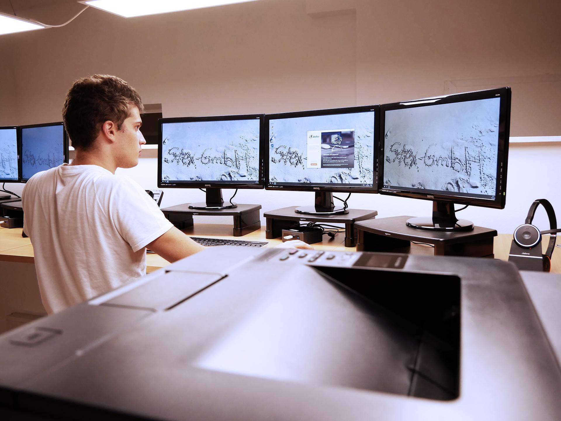 Arbeitsplatz mit drei Bildschirmen im Altag
