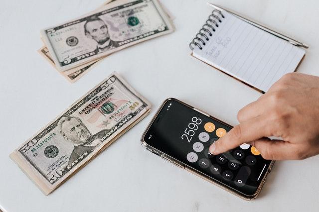 Handy mit Taschenrechner, Papierblock und Geldscheine